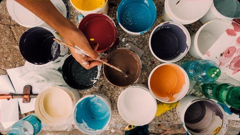 Eri värisiä maaleja ja pensseli kädessä