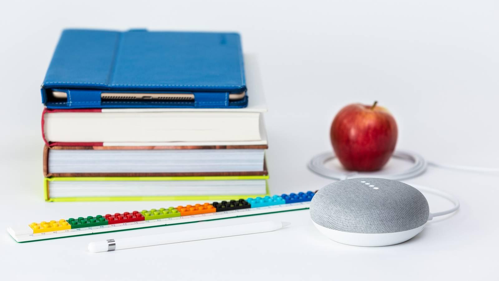 Pino kirjoja, omena ja muuta tavaraa tasolla.
