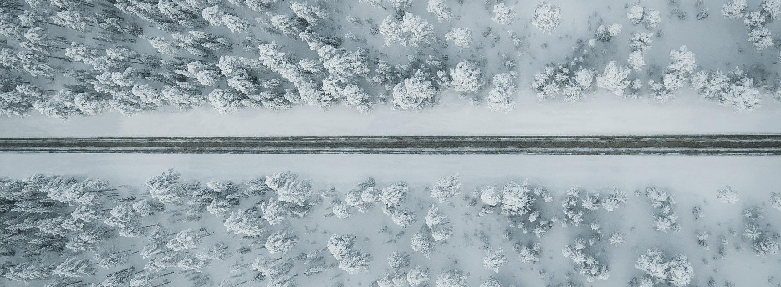 Talvinen maisema ylhäältäpäin kuvattuna, jossa keskellä tie ja ympärillä lumista metsää