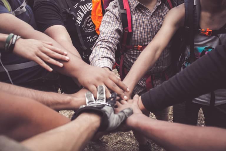 Joukko ihmisiä, jotka laittavat kätensä toisten käsien päälle piirin keskelle