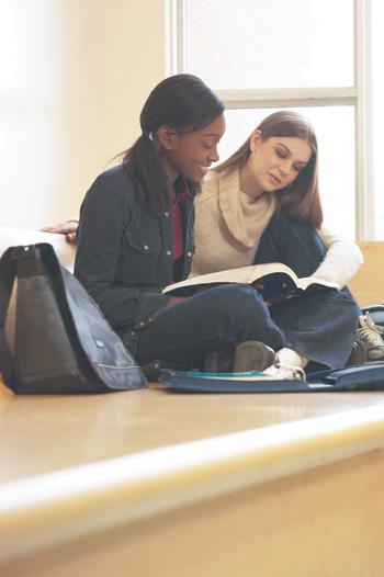Kaksi hymyilevää tyttöä lukemassa kirjaa yhdessä