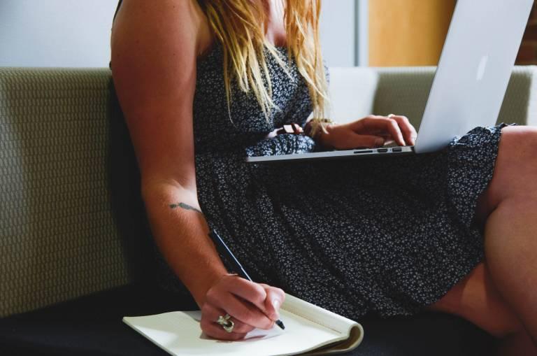 Nainen, joka näppäilee kannettavaa tietokonetta ja kirjoittaa kynällä vihkoon