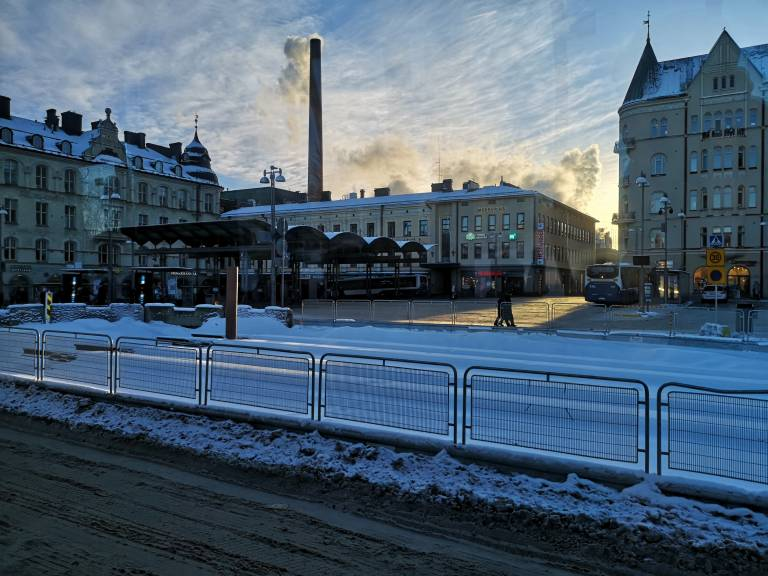 Tramline next to Keskustori square, snow in the ground, silhouettes of buildings against the setting sun