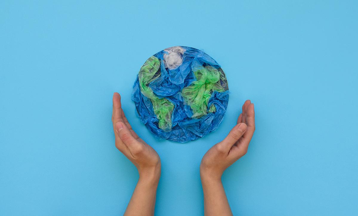 Kädet kohottautuvat kohti muovista puristettua maapalloa.