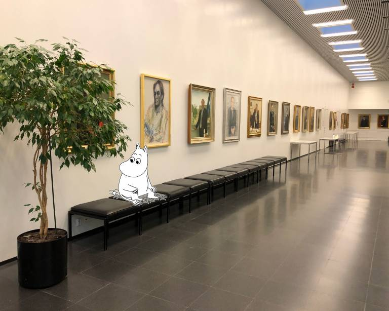 Moomintroll sitting in university lobby.