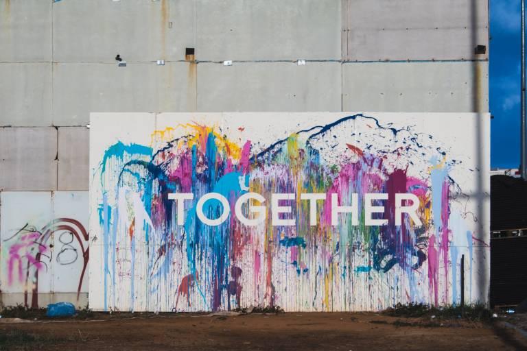 Värikäs graffittiseinä, jossa lukee Together.