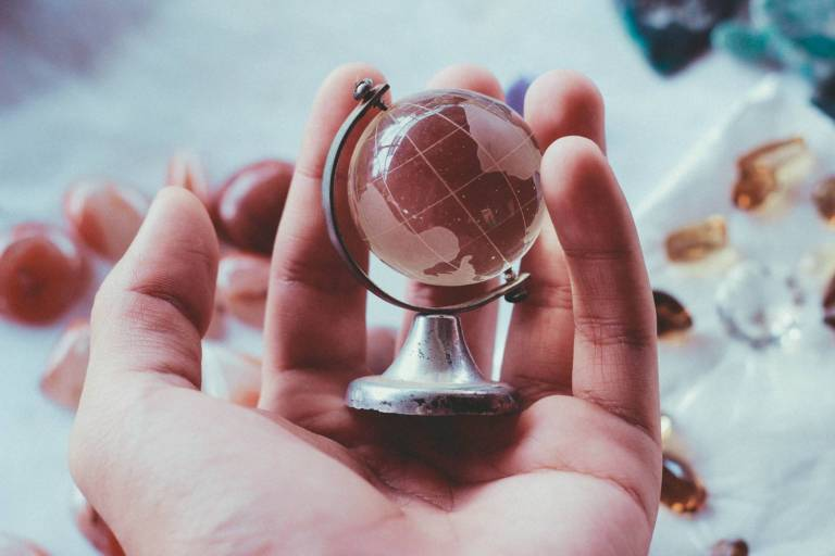 Käsi pitelee lasista maapalloa.