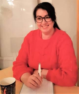 Terhi hymyilee pöydän äärellä.