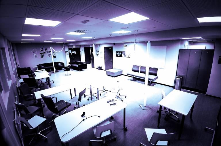 Kuva, jossa avoin luokkatila, istuimia ja työskentelypöytiä