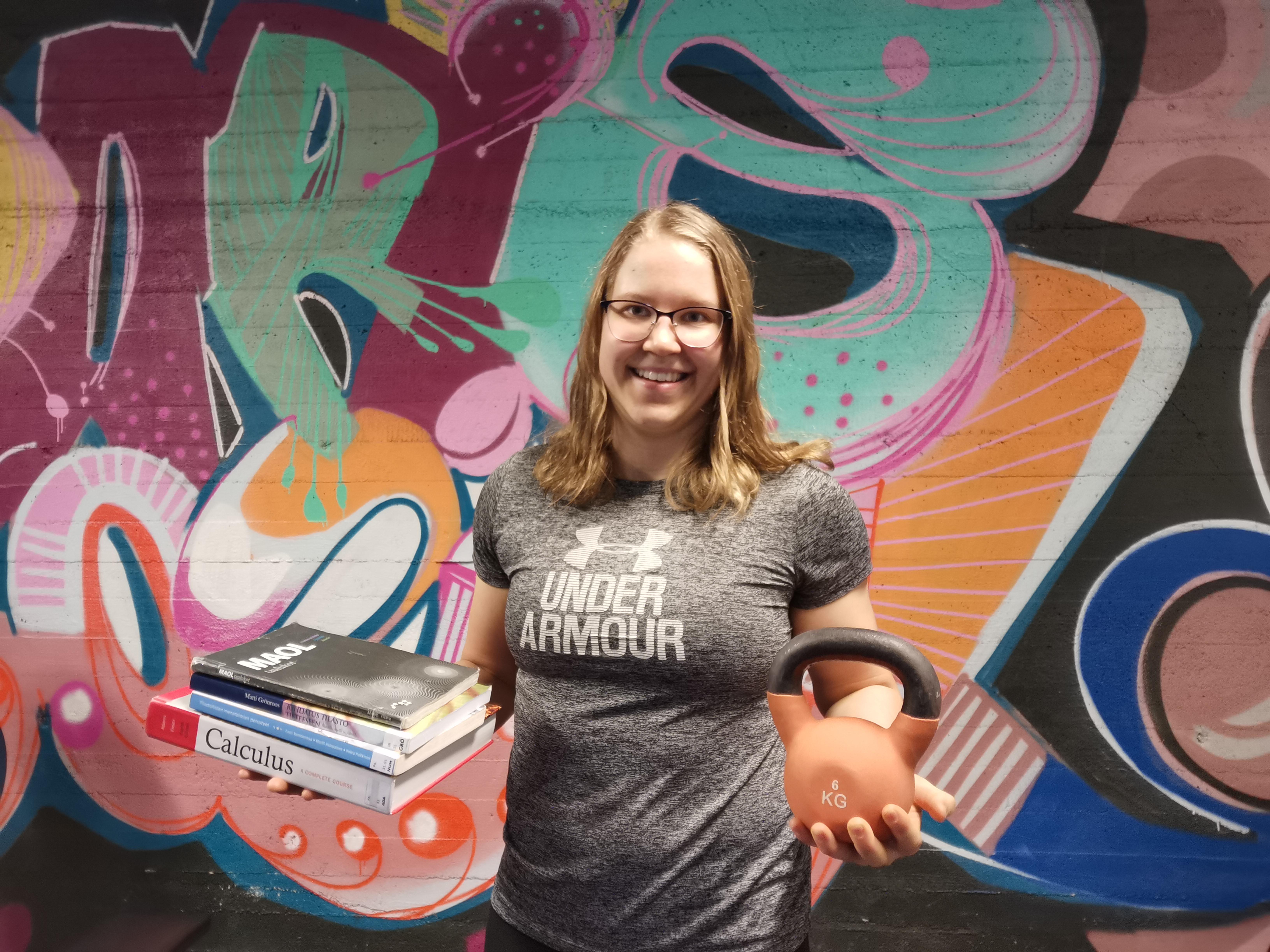 Johannalla toisessa kädessä kirjoja ja toisessa kahvakuula.