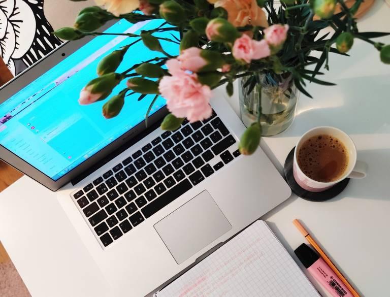 Kirjoituspöydällä värikäs kukkakimppu, kuppi kahvia, muistiinpanovihko, kyniä sekä kannettava tietokone.