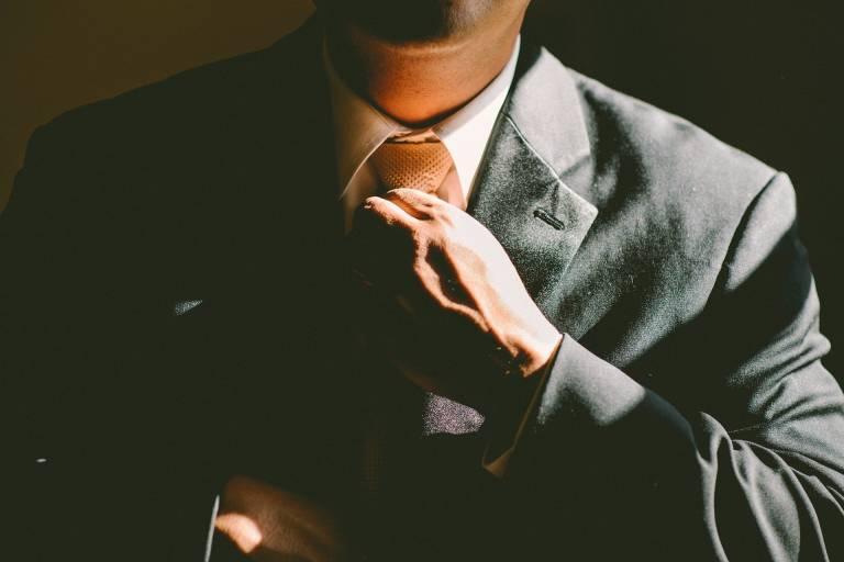 Mies puvussa kiristää kravattiaan