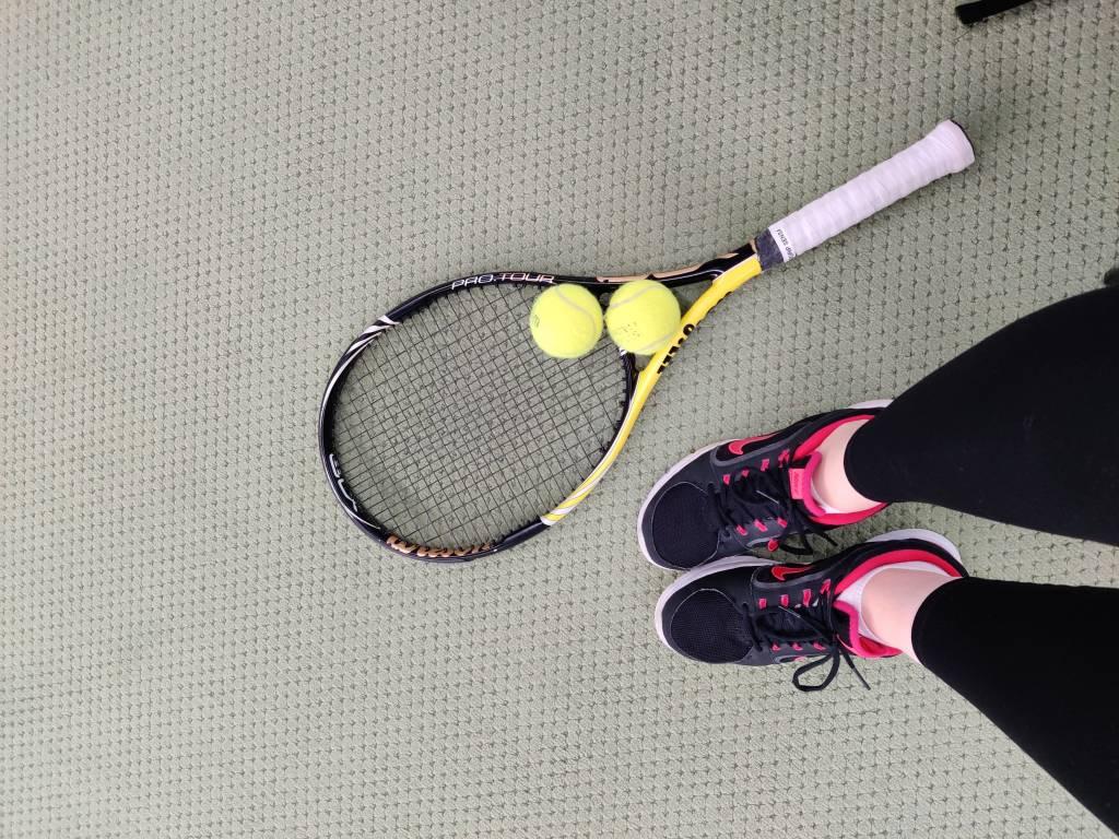 Ylhäältä otettu kuva, jossa näkyy kuvaajan jalat, tennismaila ja kaksi tennispalloa.