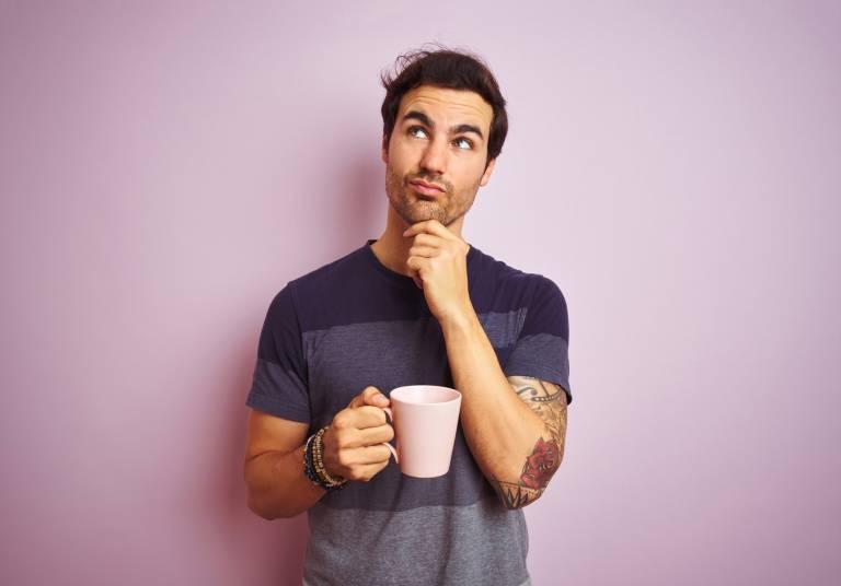 Mies pohtii jotain kahvikuppi kädessään