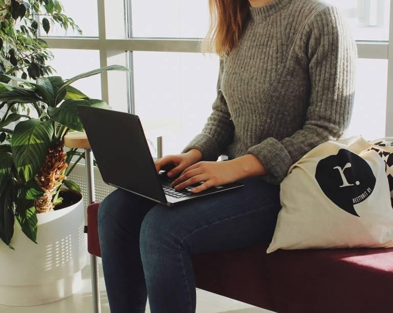 Opiskelija istuu tietokone sylissään