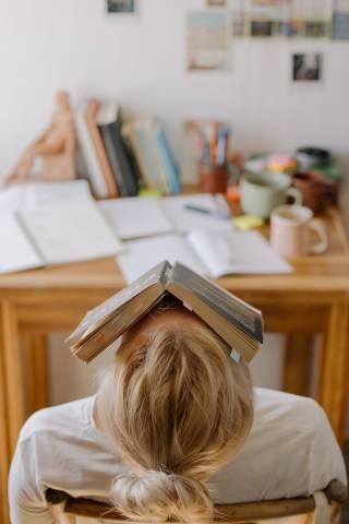 Opiskelija istuu pöydän äärellä kirja päänsä päällä