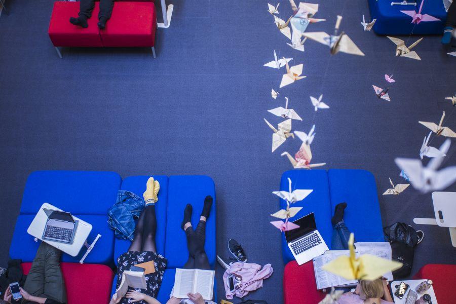 TAMKin kirjasto ylhäältäpäin, kuvassa näkyy opiskelijoita penkeillä sekä katosta roikkuvat origamit.