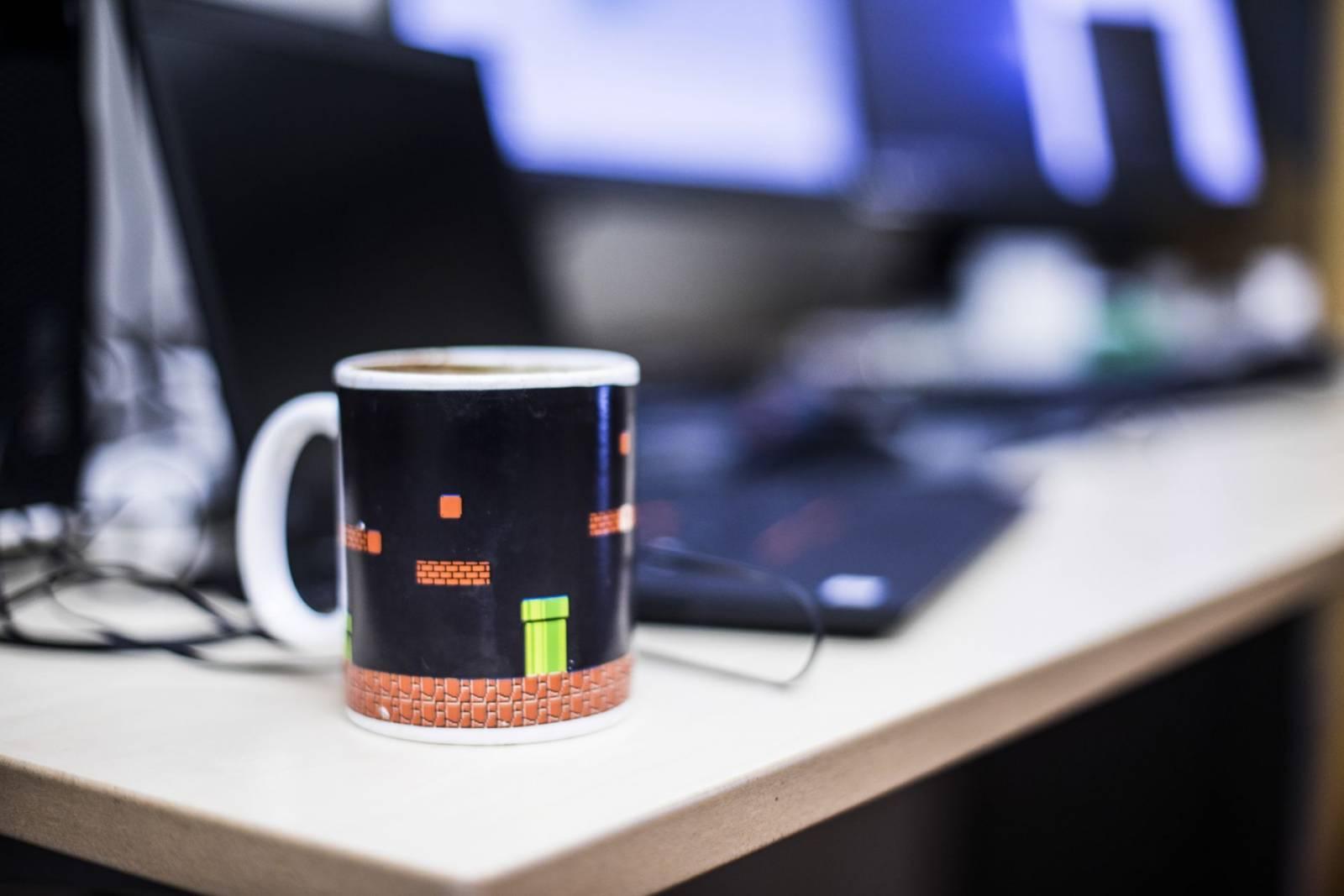 Kahvikuppi ja kannettava tietokone pöydällä.