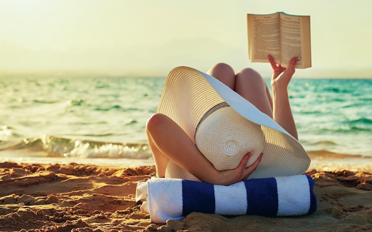 Ihminen makoilee meren rannalla.