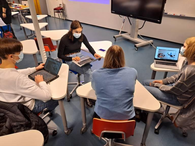 Opiskelijat suunnittelevat luokassa oppimisympäristöä pienryhmässä tietokoneiden kanssa.