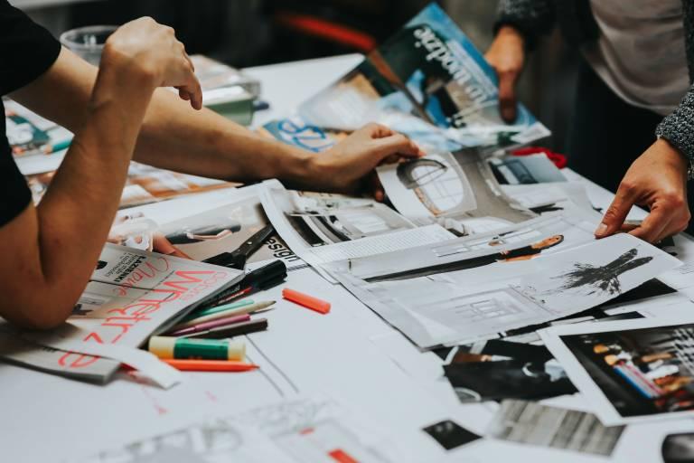 Pöytä, jonka päällä värikyniä, paperia, leikkeleitä ja käsiä, jotka selailevat lehtiä