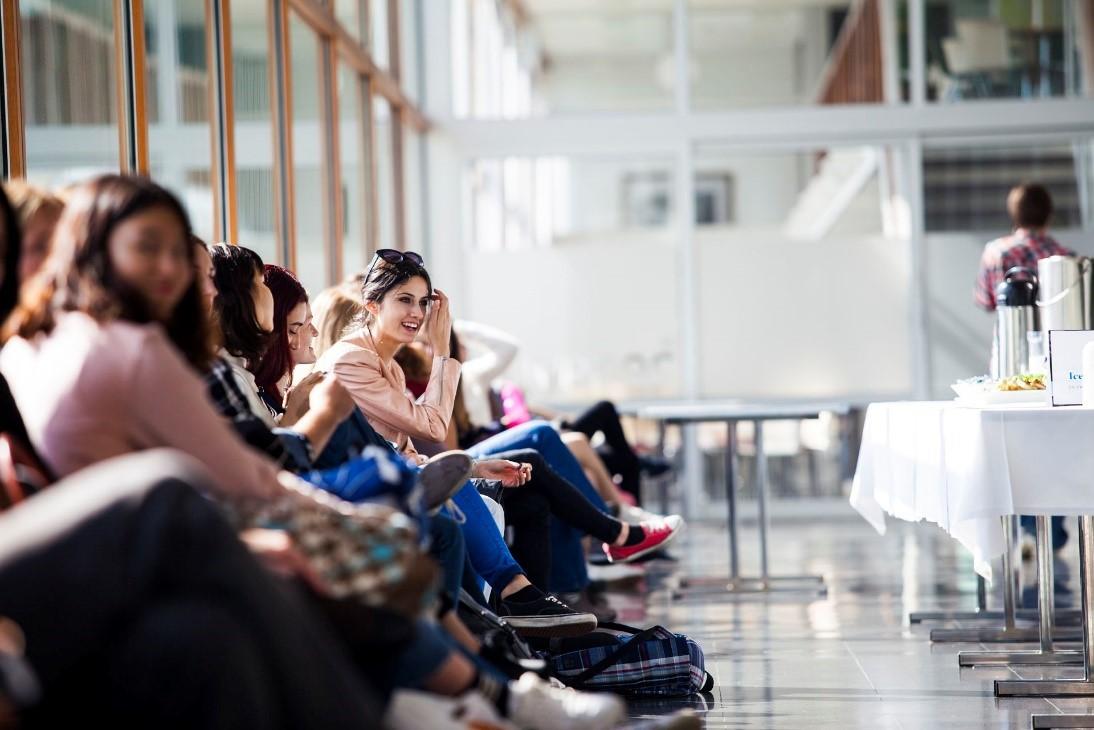 Opiskelijoita istumassa aulan penkeillä.