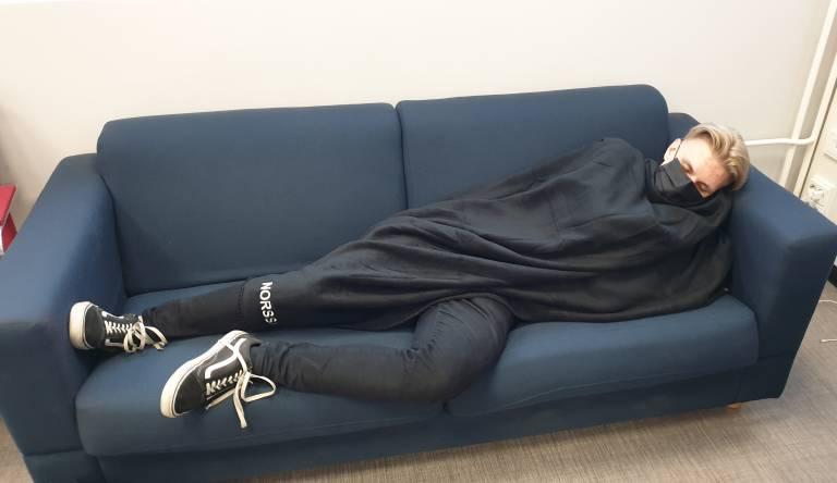Opiskelija nukkuu sohvalla viltin alla Tampereen norssin lukiossa.