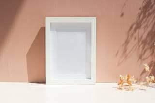 Kuva, jossa rusehtavalla taustalla valkoinen valokuvakehys, joka on tyhjä.