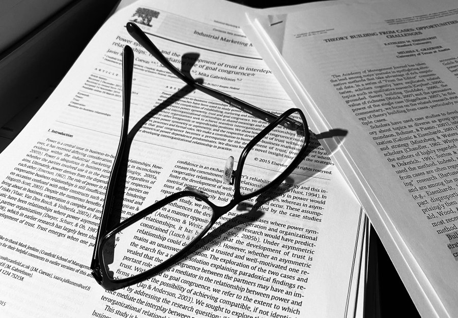 Tieteellisen artikkelin päällä mustasankaiset silmälasit.
