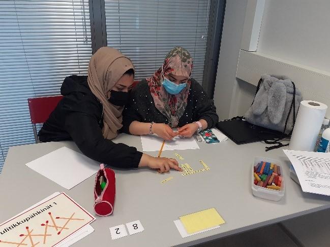 Kaksi opiskelijaa istuu vierekkäin ja tekee matematiikan tehtäviä.