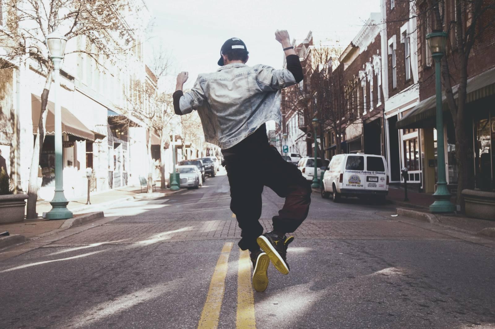 Kuva, jossa nuori hyppää ilmaan kadulla.