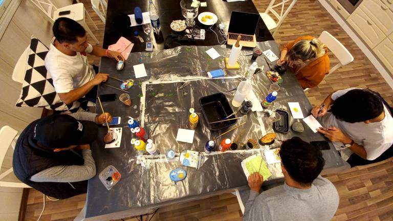 young men sitting around a table in an art workshop