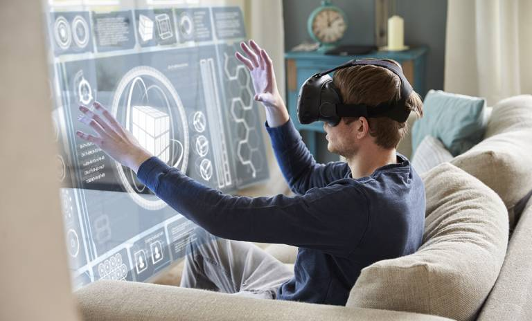 Ihminen istuu sohvalla virtuaalilasit päässään ja tutkii virtuaalista näyttöä.
