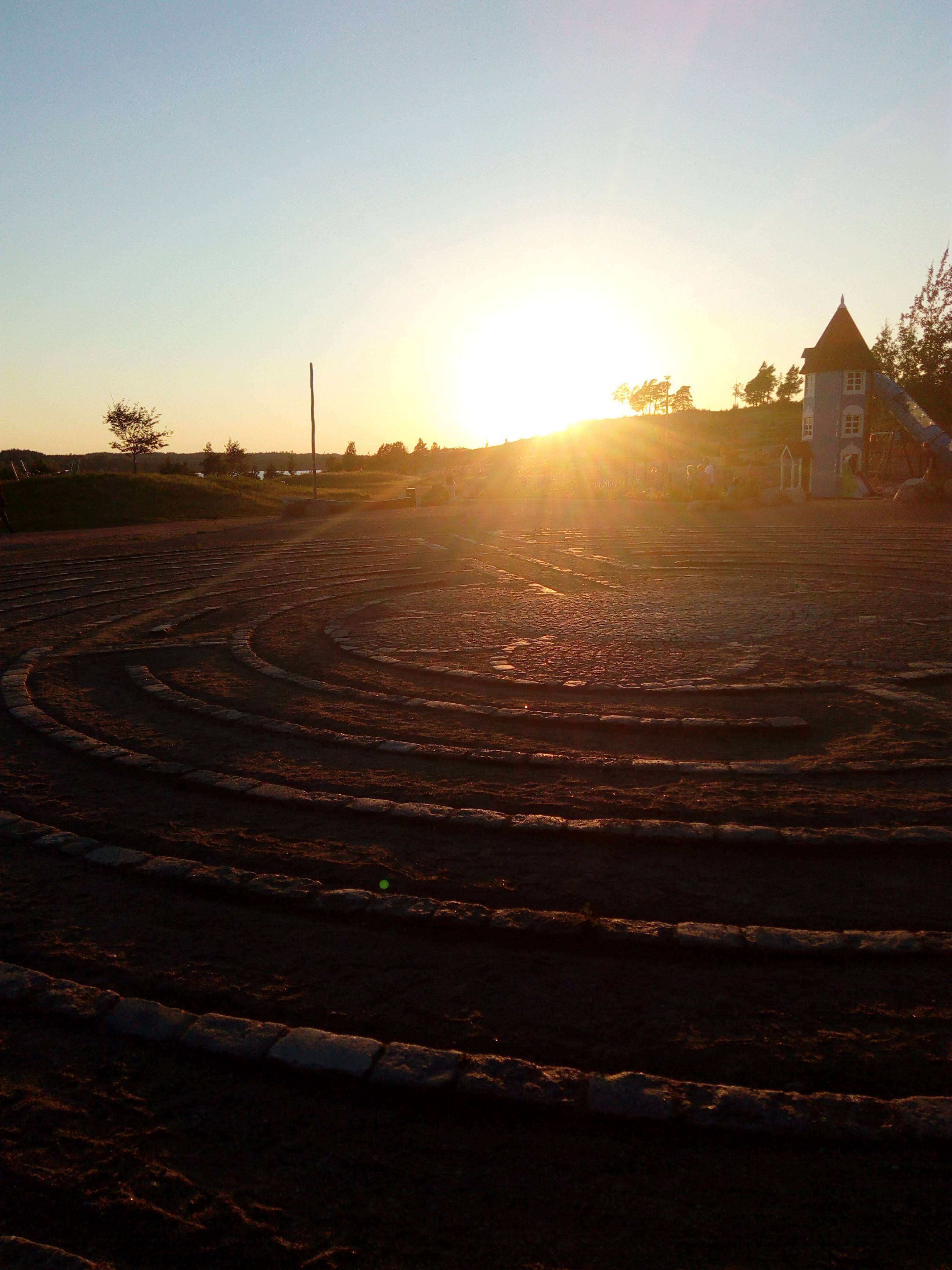 Maassa kivistä rakennettuja rengaskuvioita, taustalla auringonlasku.