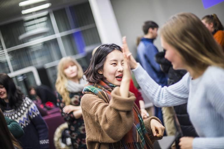 Kansainvälisten opiskelijoiden tilaisuus korkeakoulukampuksella, opiskelijoiden high five.
